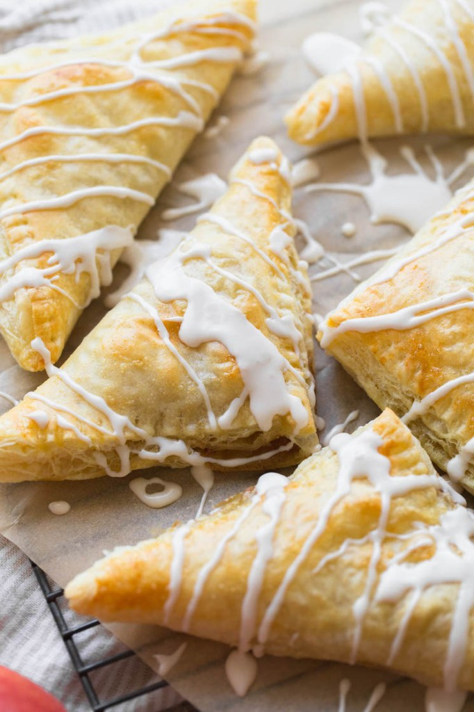 An up close image of apple turnovers topped with a maple cinnamon glaze.