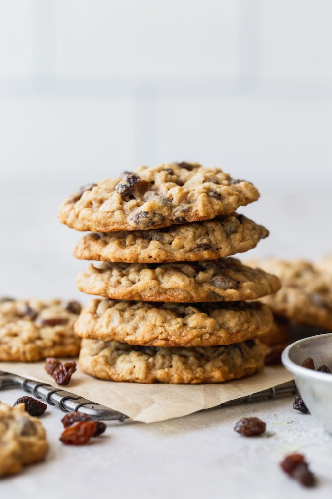 A stack of oatmeal raisin cookies on a cooling rack lined with parchment paper.