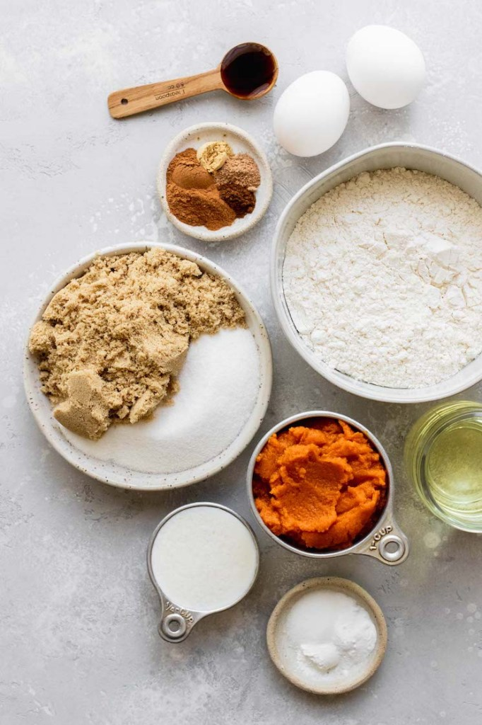 The ingredients needed to make pumpkin bread displayed in bowls and sitting on top of a rustic gray surface.