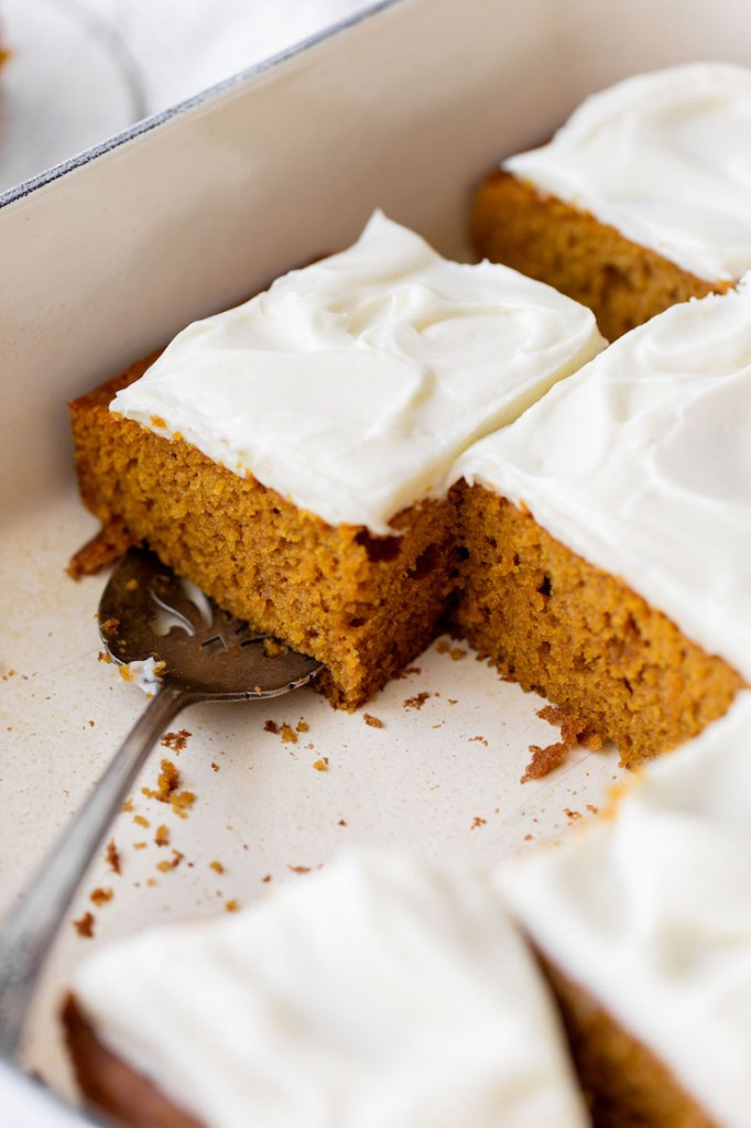 A baking dish holding a pumpkin cake with several pieces removed.
