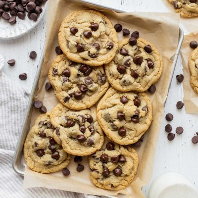 A pile of chocolate chip cookies on a baking sheet lined with parchment paper surrounded by more cookies and chocolate chips.
