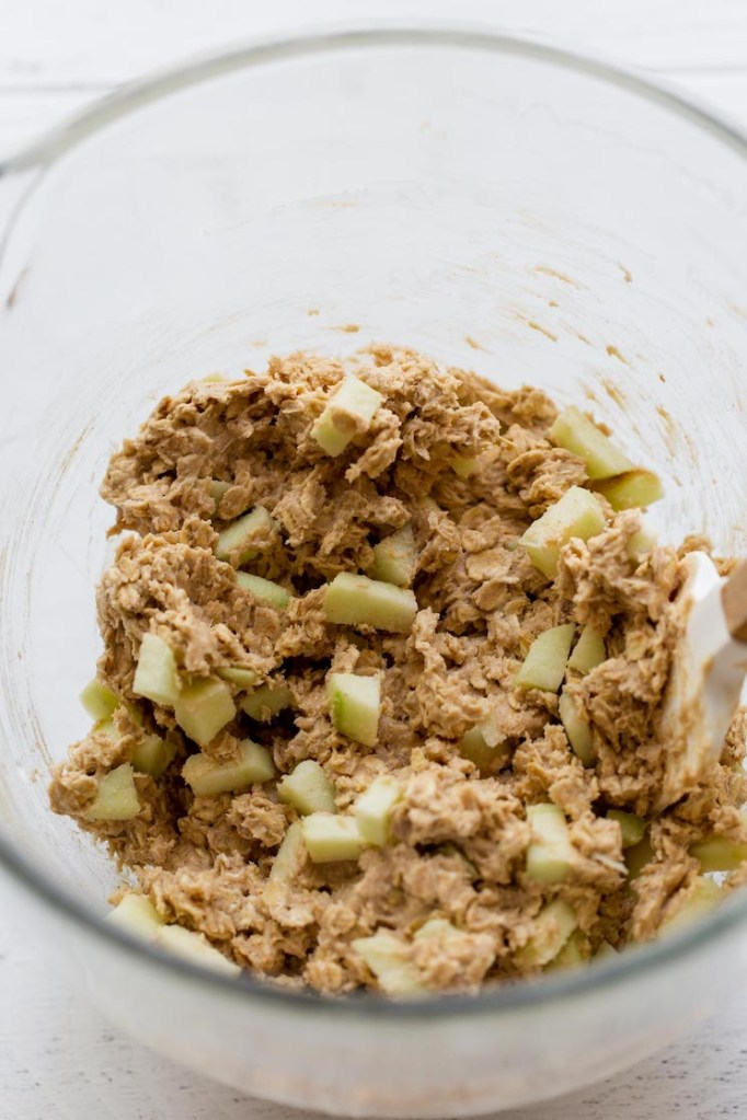 A glass mixing bowl holding cookie dough with chopped apples folded into it.
