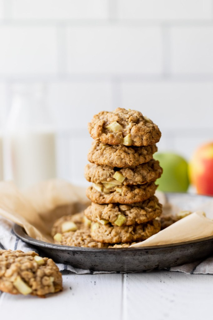A stack of apple oatmeal cookies resting in a metal baking dish. A container of milk and a couple of apples rest in the background.