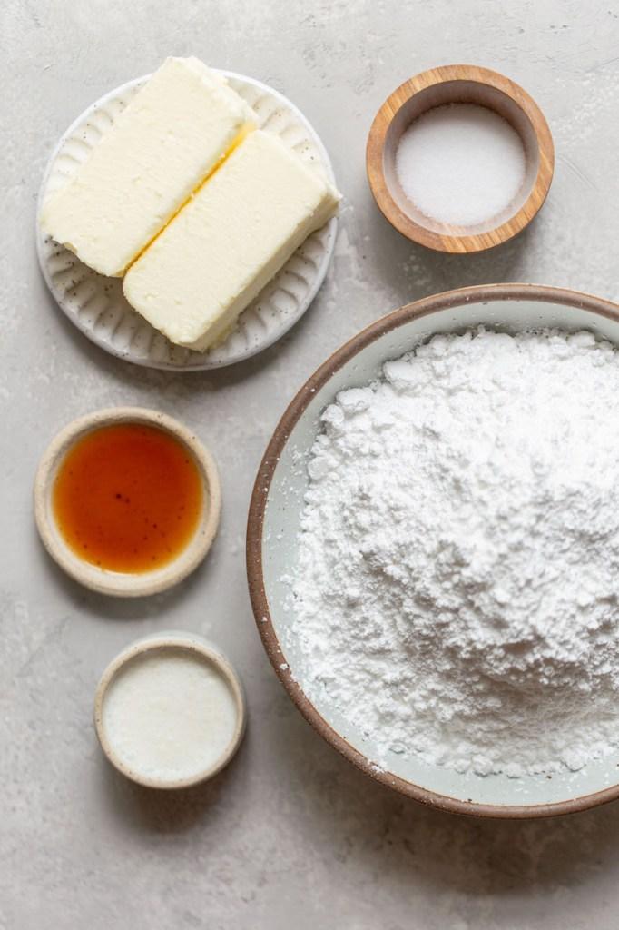 Os ingredientes necessários para fazer um lote de gelado de creme de manteiga colocado em pratos sobre uma superfície cinzenta.
