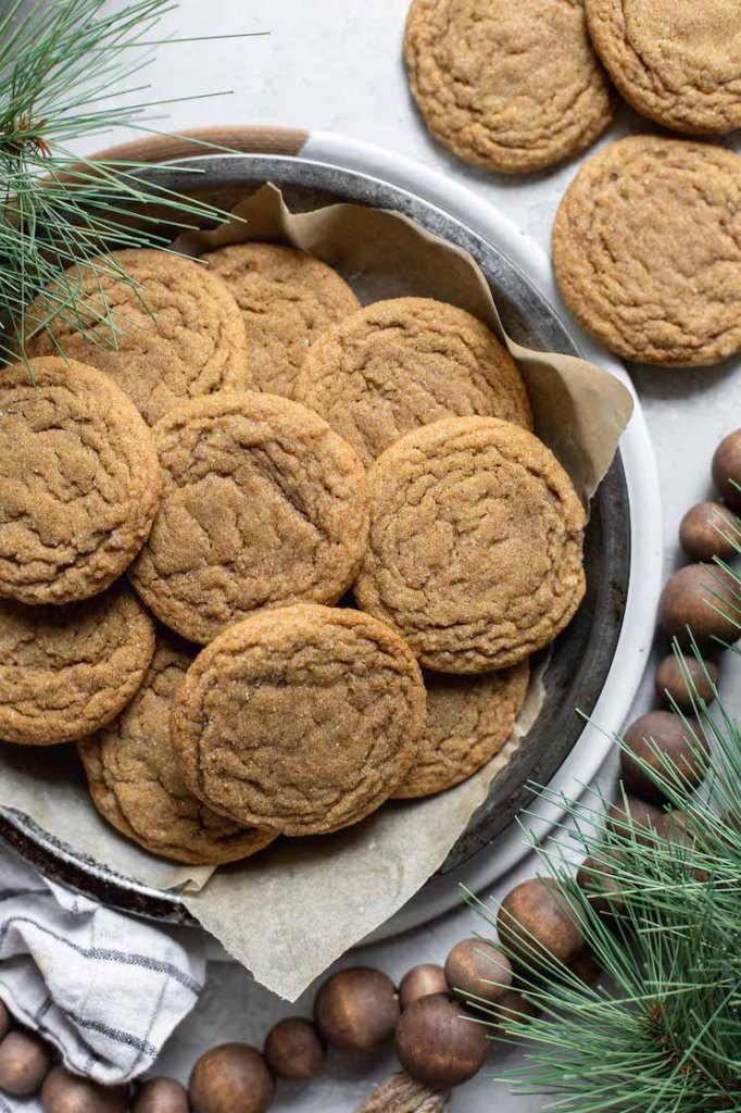 A round baking pan filled with molasses cookies surrounded by rustic Christmas decorations.