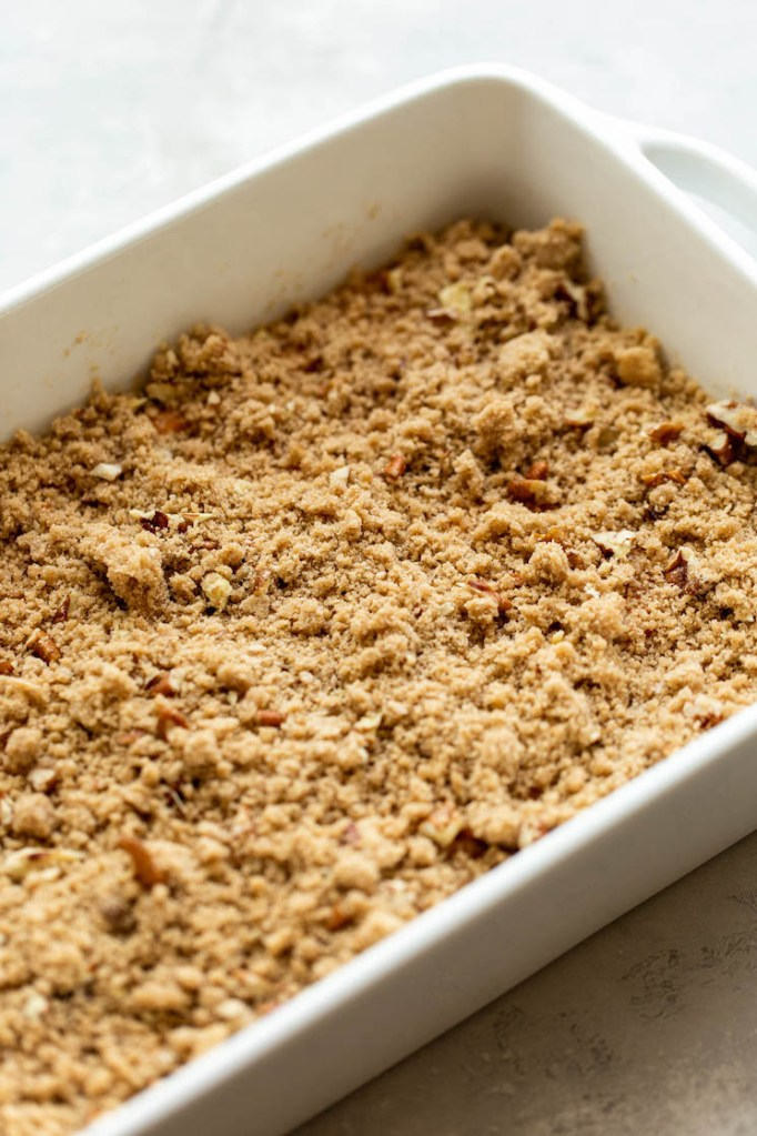 A sweet potato casserole topped with pecan streusel ready to go into the oven.