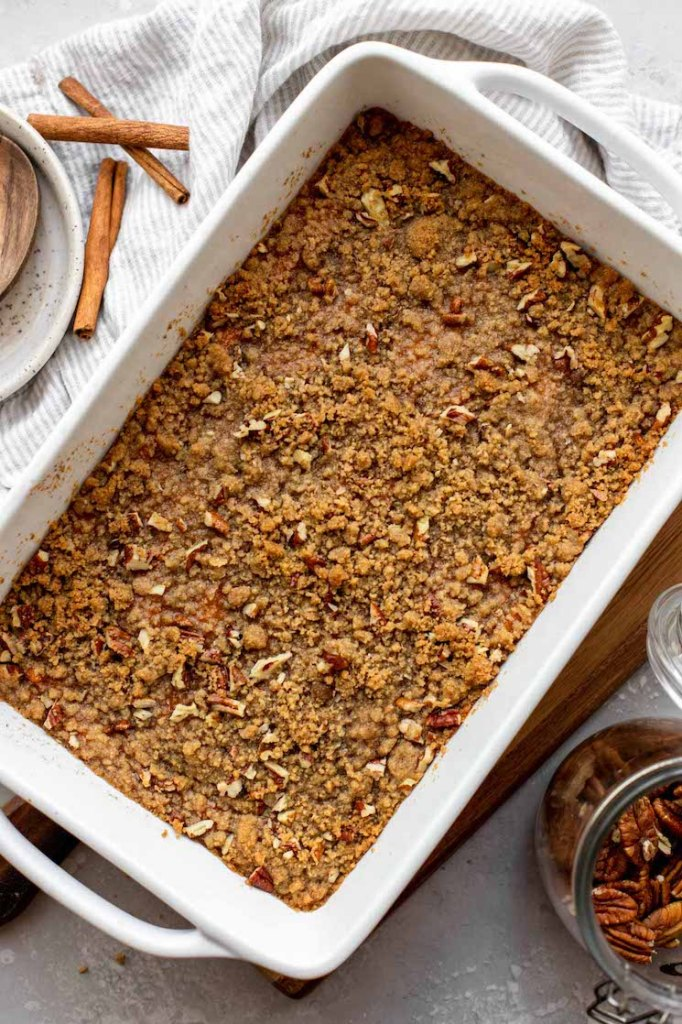 A baking pan filed with a finished sweet potato casserole topped with a pecan streusel.