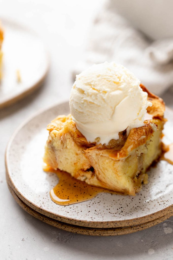 A slice of bread pudding topped with a scoop of ice cream on a white speckled plate.