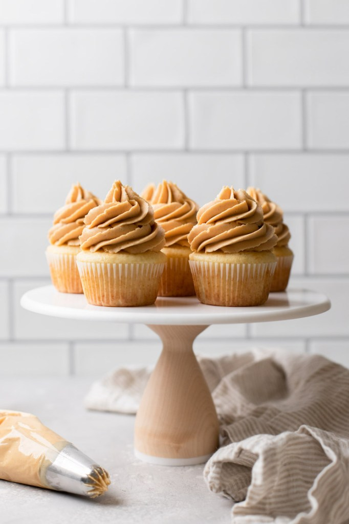 A marble cake stand holding vanilla cupcakes topped with peanut butter frosting and a piping bag of frosting off to the side.