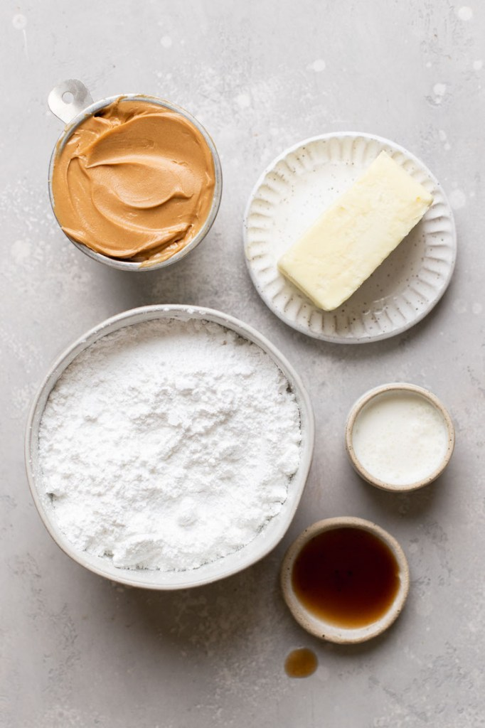 The ingredients needed to make peanut butter frosting laid out on a gray surface.
