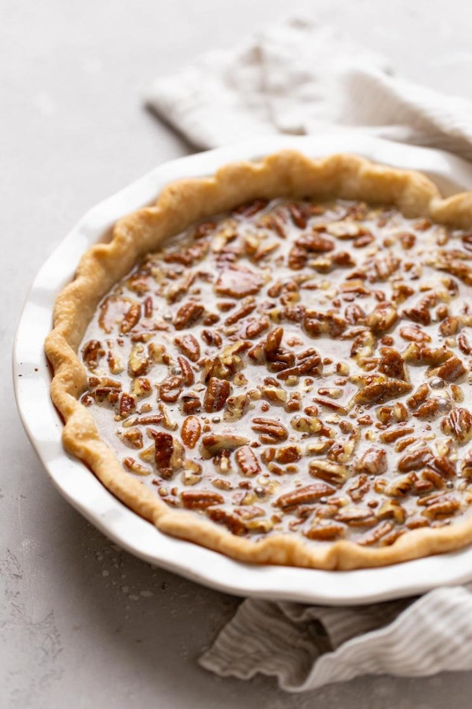 A pecan pie in a white baking dish ready to be put into the oven.