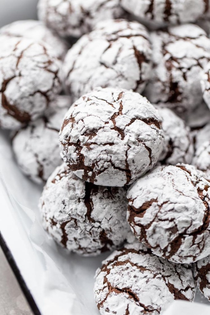 A serving dish filled with chocolate crinkle cookies.