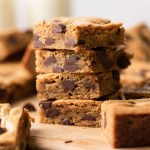 A stack of four chocolate chip cookie bars on a wood serving board. More cookie bars surround the stack.