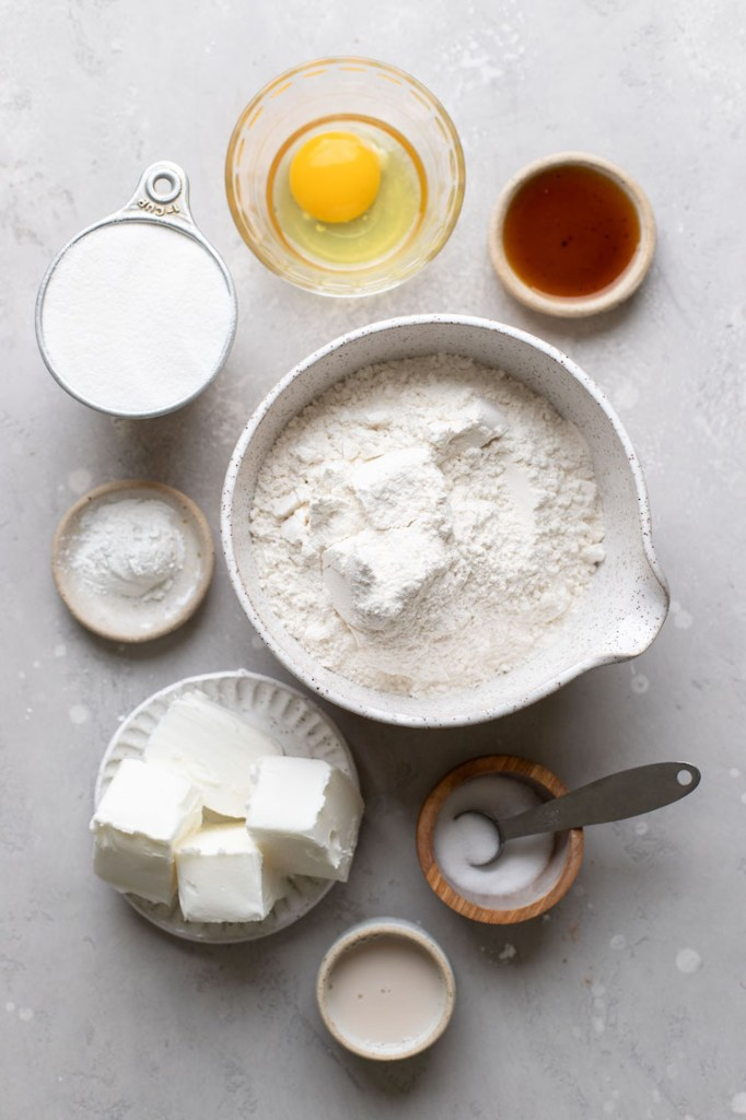 The ingredients needed to make cut-out sugar cookies laid out on a rustic gray surface.