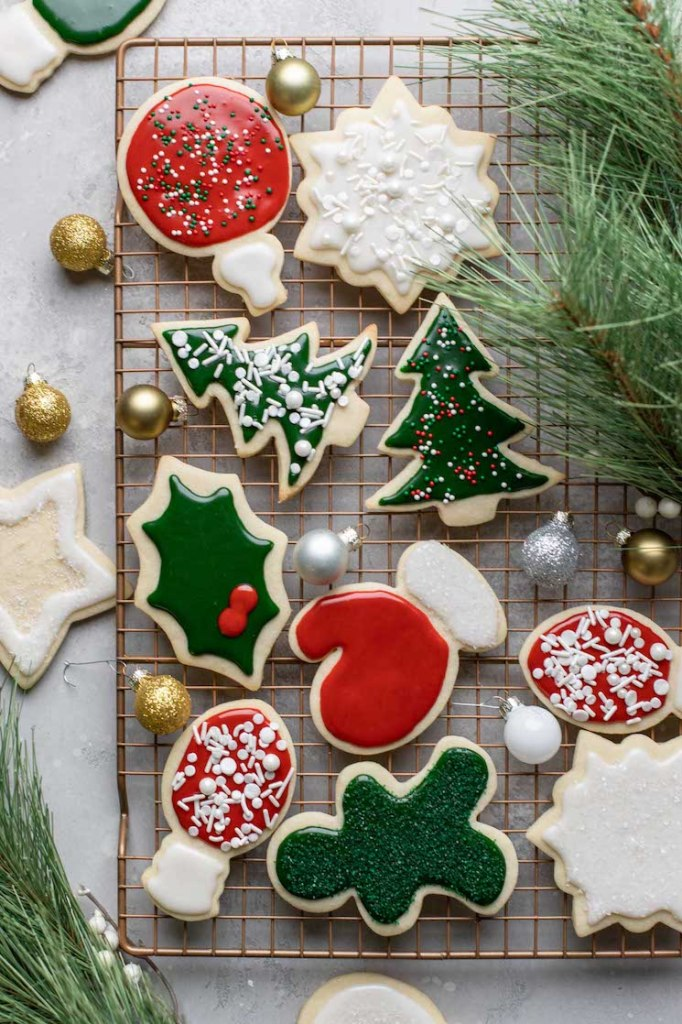 A cooling rack filled with decorated cut-out sugar cookies.