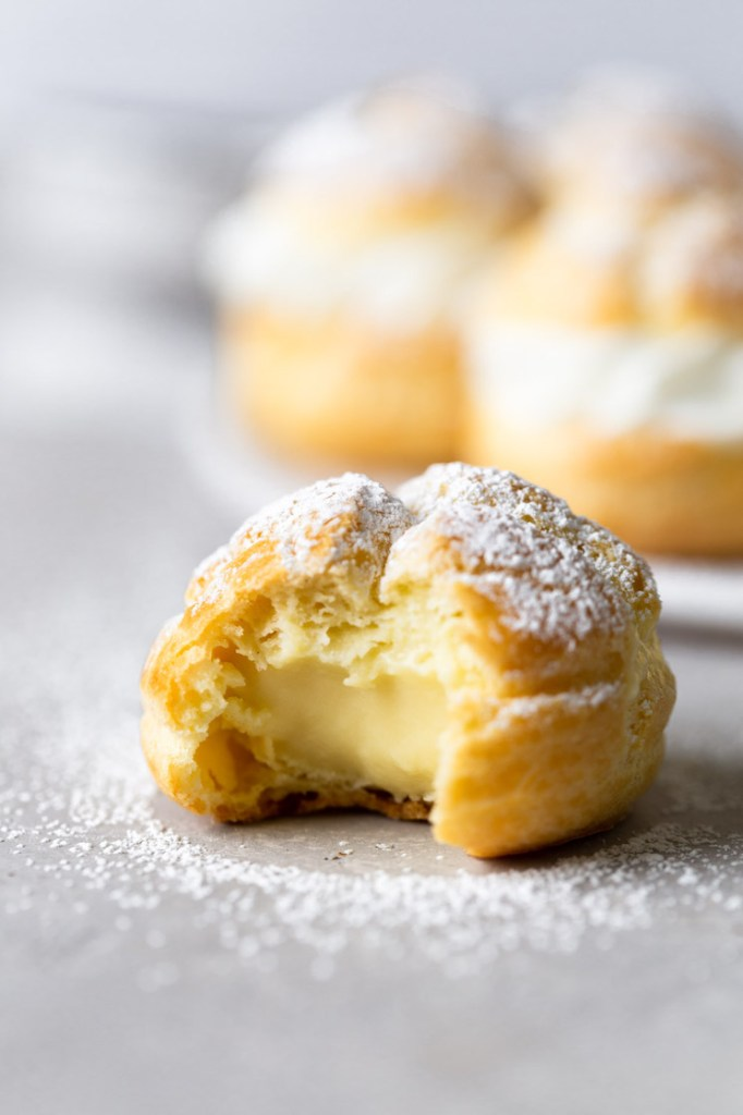 A cream puff with a bite missing. More filled cream puffs are on a plate in the background.