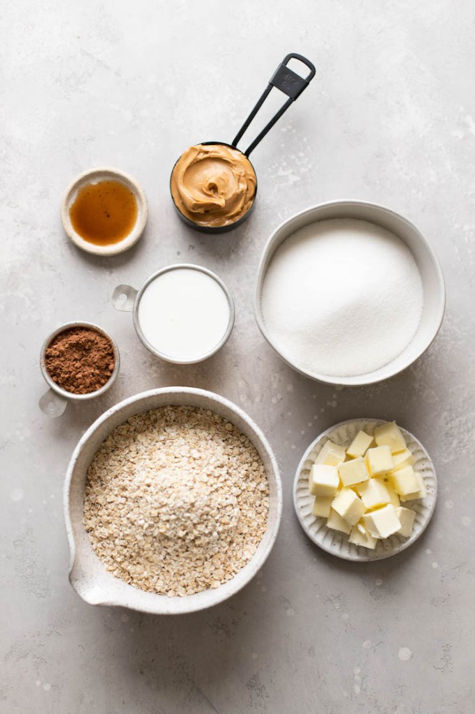 The ingredients needed to make classic no-bake cookies in different bowls and measuring cups on a gray surface.