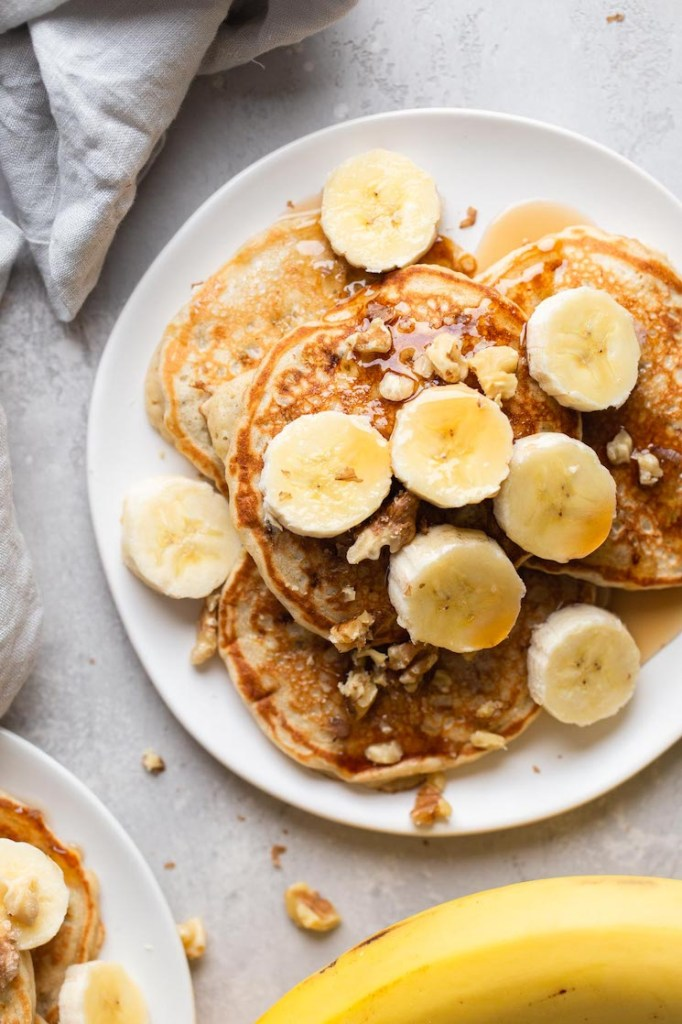 Overhead view of fluffy banana pancakes topped with banana slices and chopped walnuts on a white plate.