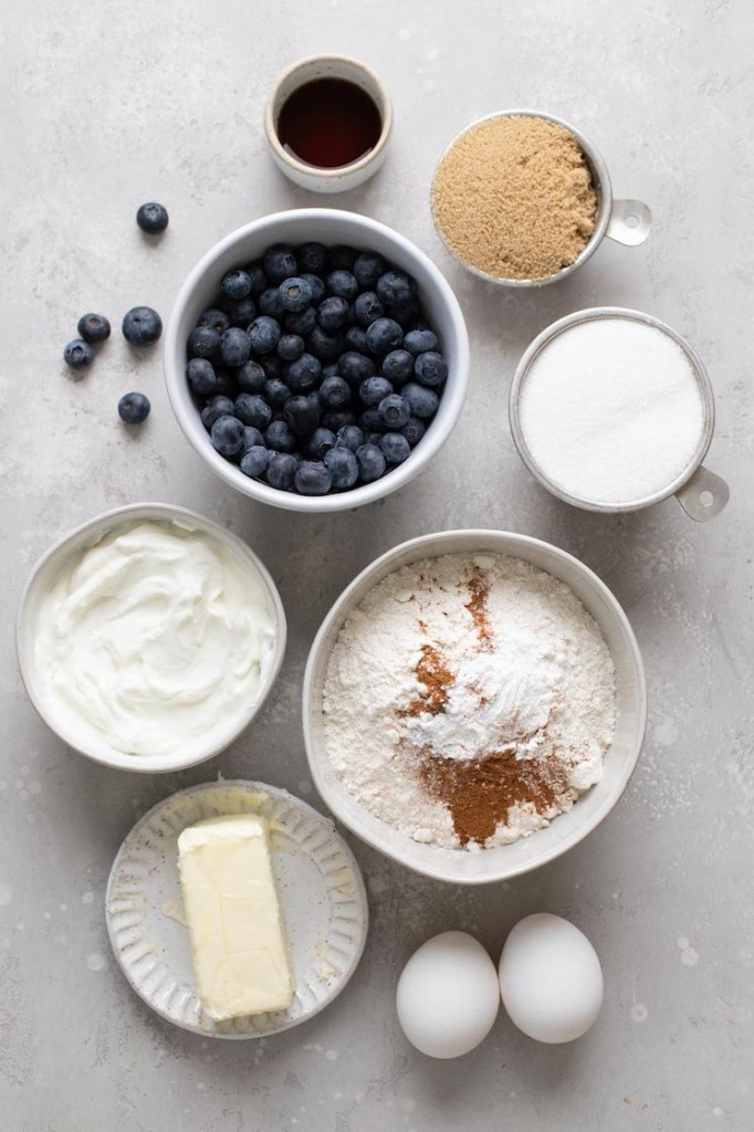 An overhead view of the ingredients needed to make a blueberry sour cream coffee cake.