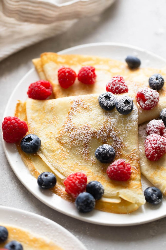 Three crepes topped with berries and dusted with powdered sugar on a white plate. A towel is in the background.