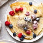 Overhead view of three homemade crepes topped with fresh berries and dusted with powdered sugar on a white plate.