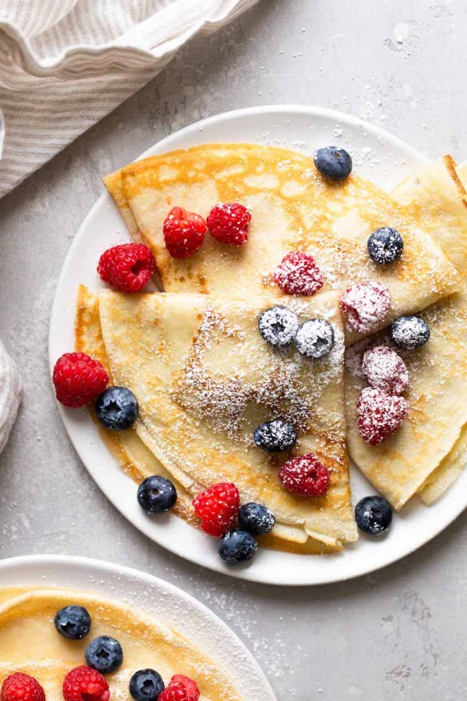 Overhead view of three homemade crepes topped with fresh berries and dusted with powdered sugar on a white plate. Another plate of crepes is partially seen in the lower left corner.