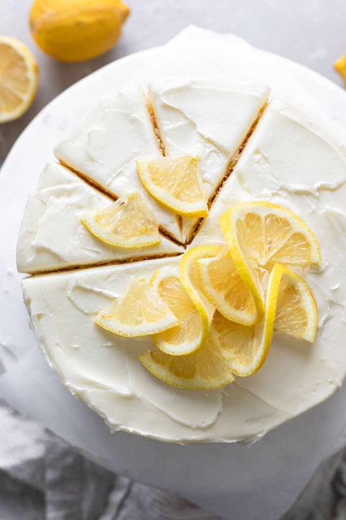 An overhead view of a lemon layer cake on a cake stand. Three slices have been cut but not yet removed from the cake.
