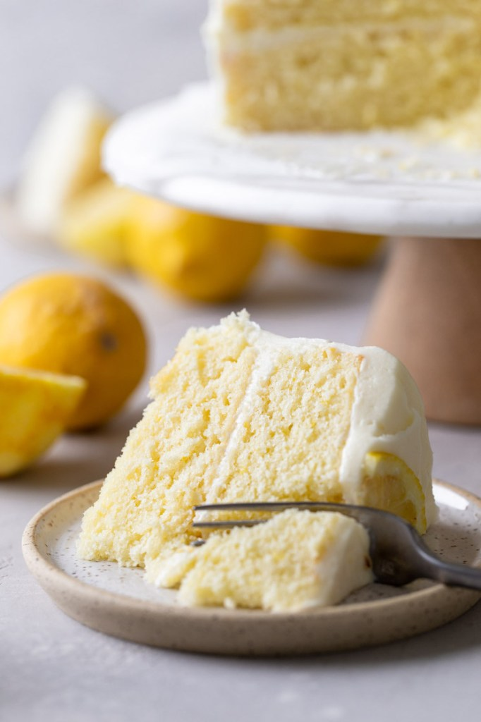 A slice of homemade lemon cake lying on its side on a speckled plate. A fork is digging into the slice. The rest of the cake is on a cake stand in the background.