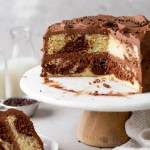 A side view of a homemade marble cake on a cake stand. A slice has been removed and has been plated. Milk jugs rest in the background.