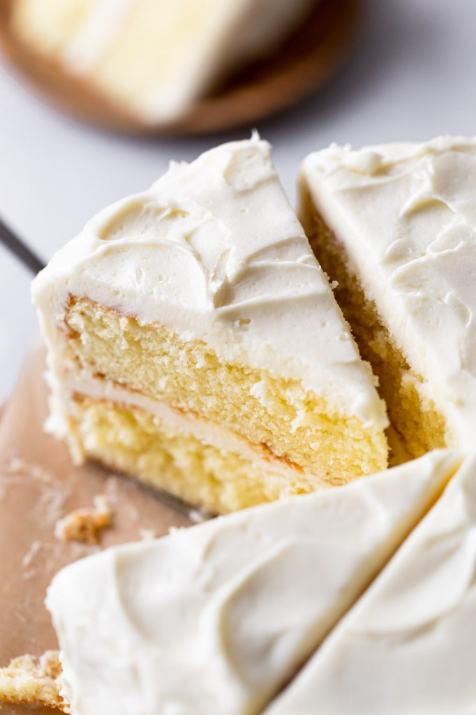 Overhead view of a sliced vanilla cake. Once slice has already been removed.