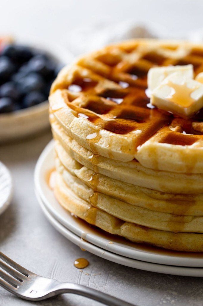 A side view of a stack of fluffy waffles topped with butter and syrup. A bowl of fresh berries rests in the background.