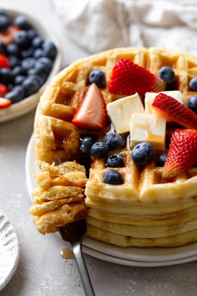 A tall stack of waffles topped with berries, butter, and syrup. A fork rests on the plate as well, speared with a big bite of waffle.