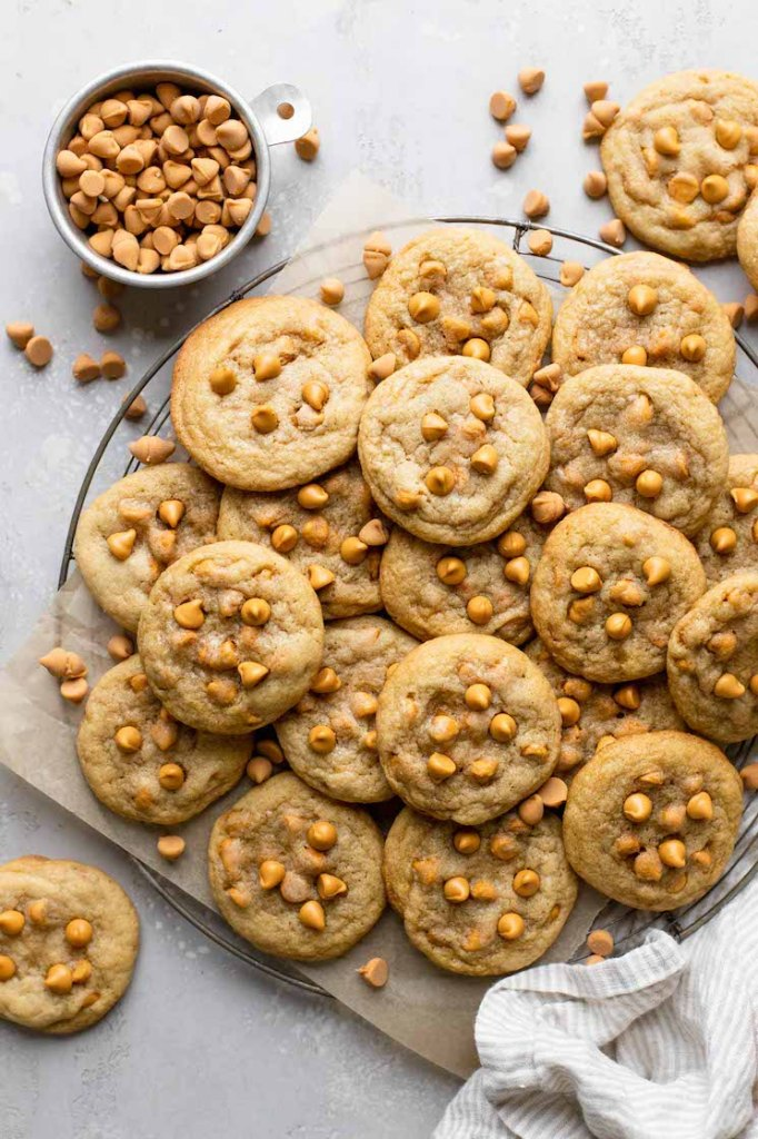 An overhead view of butterscotch cookies piled on a wire cooling rack. A dish of butterscotch chips rests on the side.