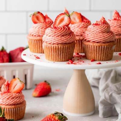 A side view of fresh strawberry cupcakes on a cake stand.
