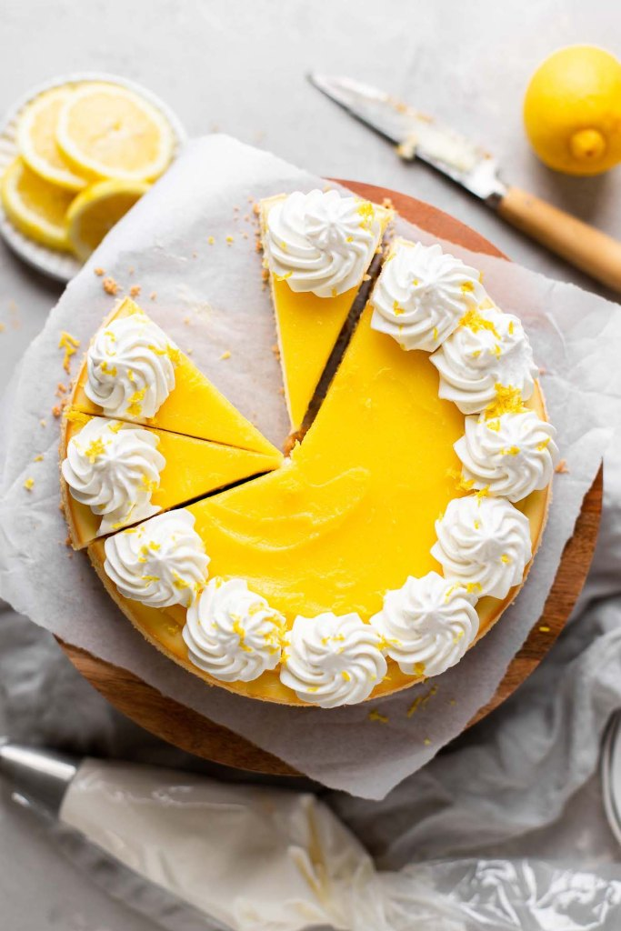 An overhead view of a lemon cheesecake on a cake stand. A few slices have been cut and one is missing.