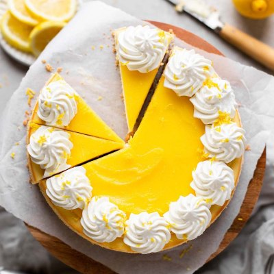 An overhead view of a lemon cheesecake topped with lemon curd and whipped cream. The cheesecake has been partially sliced and one slice has been removed.