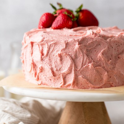 A strawberry cake with strawberry buttercream frosting sitting on top of a marble cake stand. Several fresh strawberries rest on top of the cake.