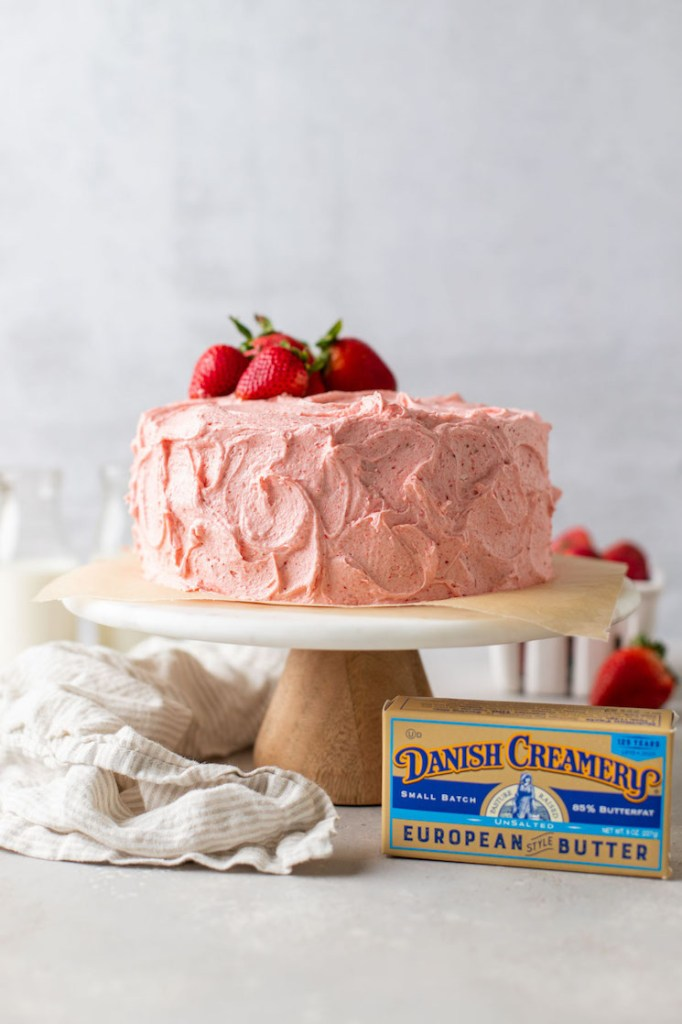 A strawberry cake topped with fresh strawberries sitting on top of a cake stand. A box of butter and a napkin are sitting next to the cake stand.