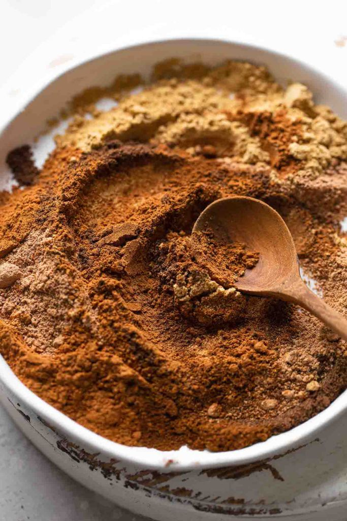 A wooden spoon mixing together the spices for pumpkin pie spice on a white dish.