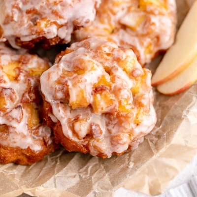 Several glazed apple fritters on top of a piece of brown parchment paper in a metal dish. A couple of apple slices are resting next to the fritters.