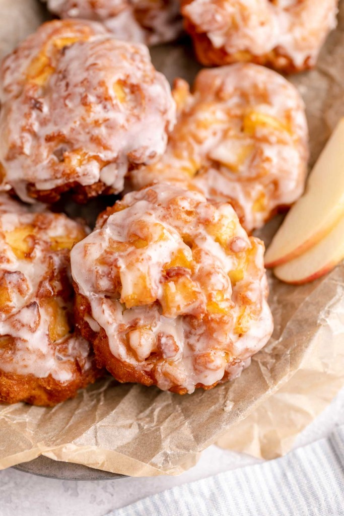Homemade apple fritters in a parchment-lined bowl.