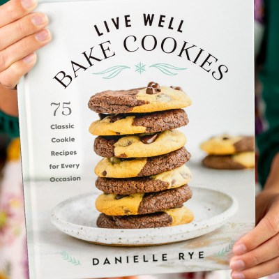 An image of the cookbook Live Well Bake Cookies being held in front of a camera.