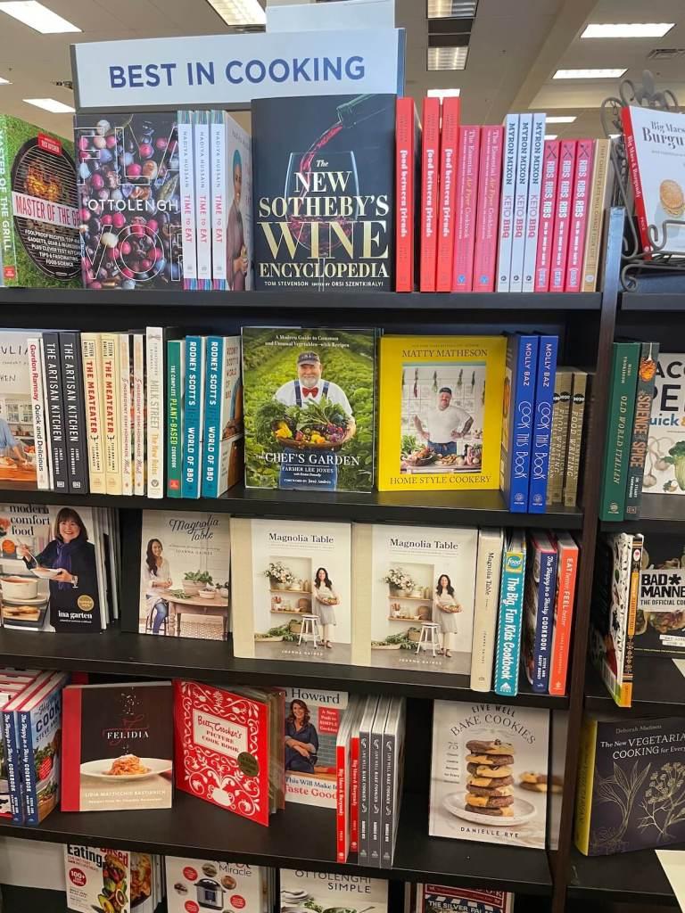 Several cookbooks on a shelf in a bookstore.