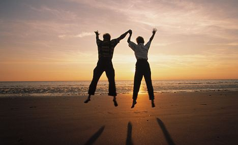 Senior Couple Jumping on Beach --- Image by © Benelux/zefa/Corbis