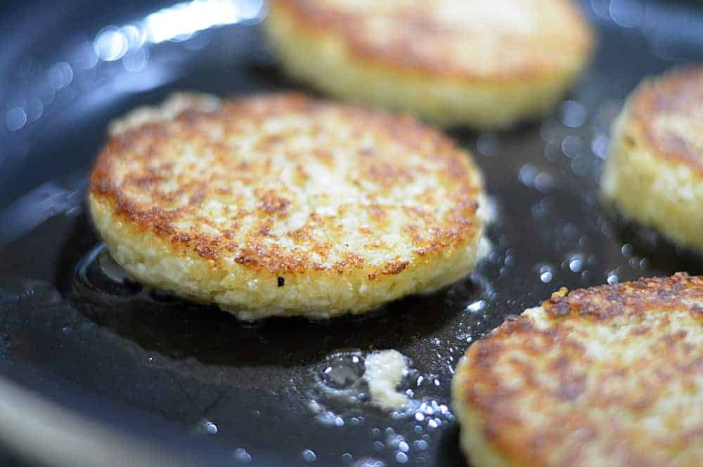 Golden Brown Cauliflower Fritters frying in a pan