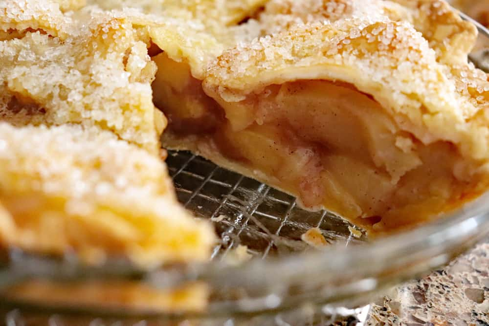 Whole apple pie with slice missing