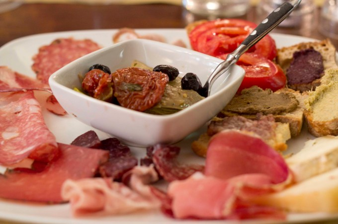 Antipasto toscano/Tuscan mixed starter of cold cuts, preserved vegetables, and toast with different spreads
