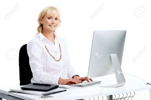 Portrait studio shot of  smiling business woman sitting at ehr desk typing at her computer