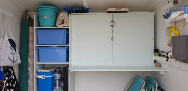 Strandcabine inrichten: handig rekje, tafeltje boven stoelen en kastje met schuifdeurtjes voor de herbruikbare borden en bekertjes.