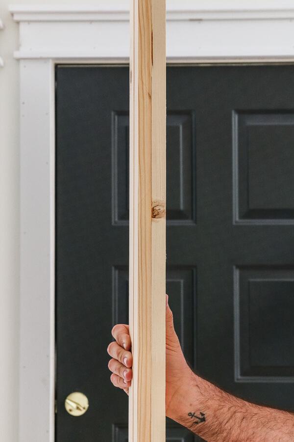 hand holding pine lumber for DIY barn door